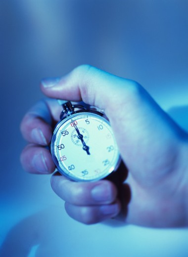 shot of a person holding a stop watch; tungsten : Stock Photo