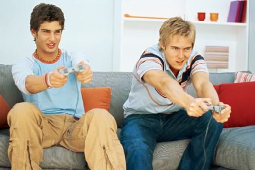 Portrait of two young men sitting on a couch and playing a video game : Stock Photo