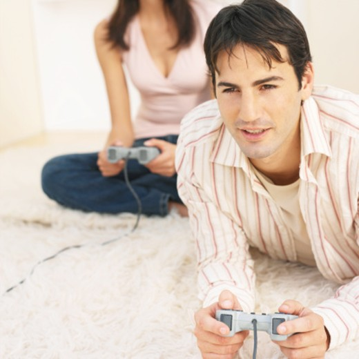 close-up of a young man playing a video game : Stock Photo
