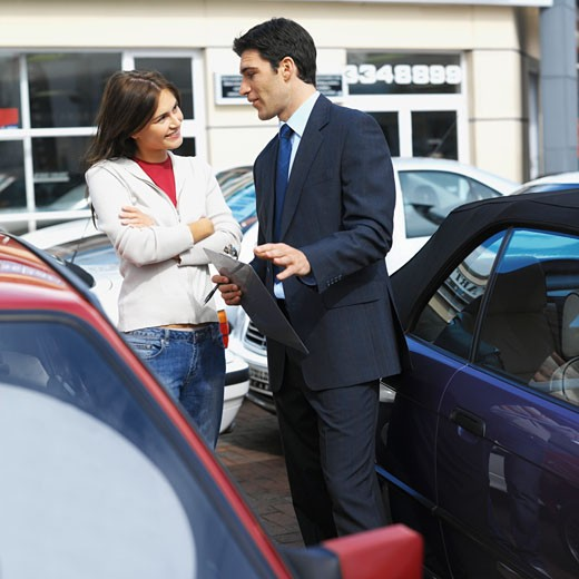Stock Photo: 1491R-1117388 Salesman with a clipboard advising a female customer on buying a car