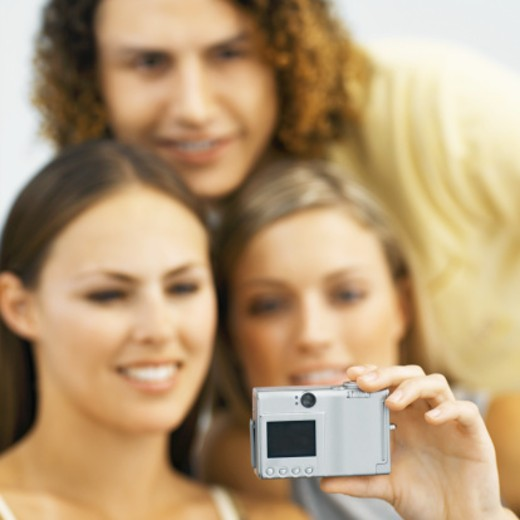Close up of three young people holding a camera and taking a photograph : Stock Photo