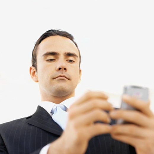 Low angle view of a businessman using a palm pilot : Stock Photo