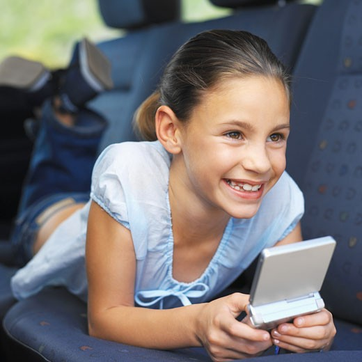 Girl (8-9) lying in the back seat of a car, playing a computer game : Stock Photo