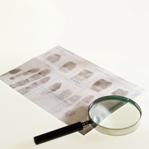 Stock Photo: 1491R-1121429 Finger prints and a magnifying glass