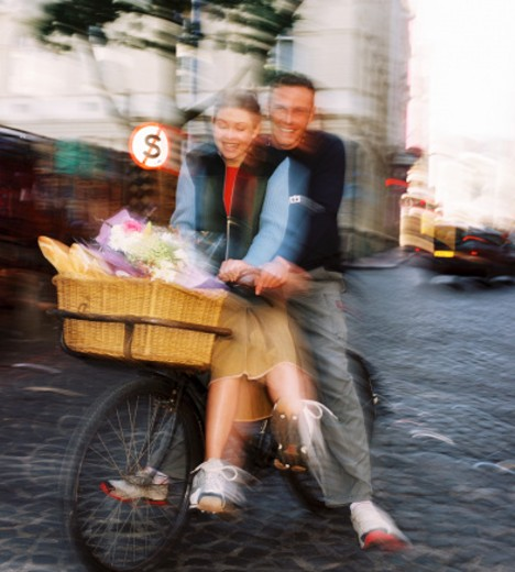 Stock Photo: 1491R-1124685 blurred view of a man riding a bicycle with a woman and a basket of bread in the front