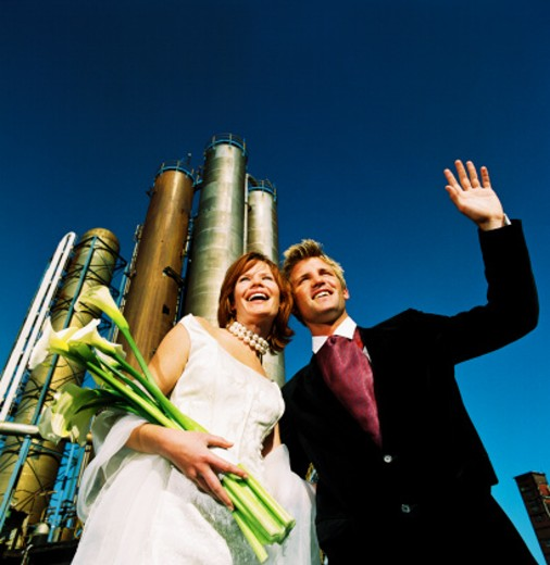 low angle view of newly weds holding flowers and waving from the base of an industrial plant : Stock Photo