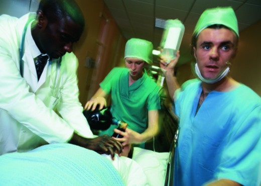 Medical personnel working on a patient on a gurney in the hospital : Stock Photo