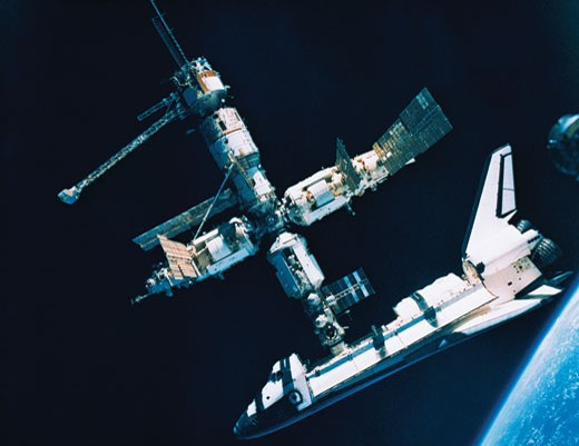 The space shuttle docked with a space station : Stock Photo