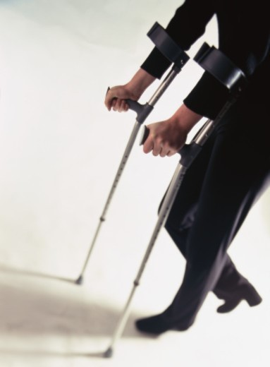 Close-up of a man using crutches : Stock Photo