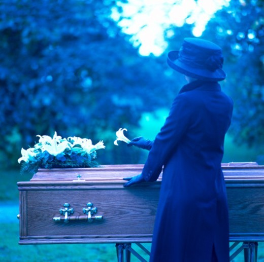 a woman placing a flower on a coffin : Stock Photo