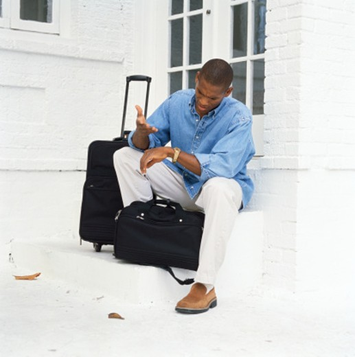 view of a young man sitting with his luggage and waiting for someone : Stock Photo