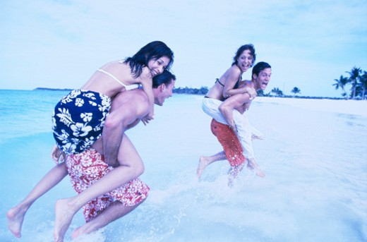 Stock Photo: 1491R-1126875 tungsten view of two young women riding piggyback on the backs of two young men