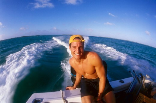 portrait of a young man sitting in a speedboat : Stock Photo