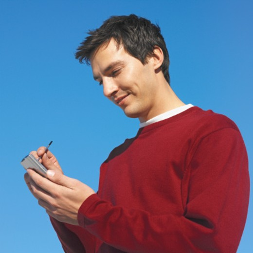 close-up of a young man using a palmtop : Stock Photo