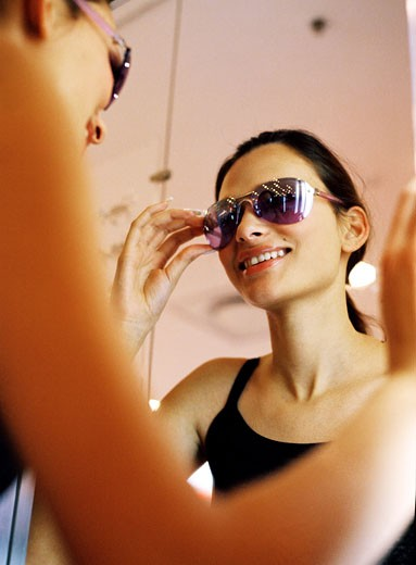 Low angle view of a young woman trying on sunglasses : Stock Photo