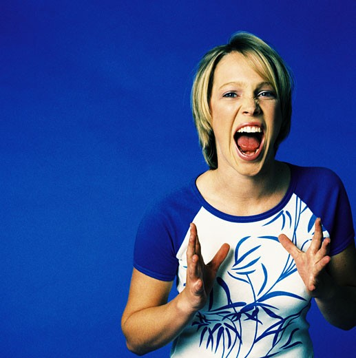 Portrait of a young woman screaming : Stock Photo