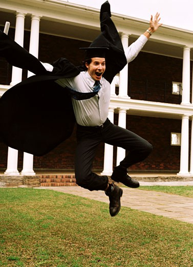 Young male graduate jumping in a university lawn : Stock Photo