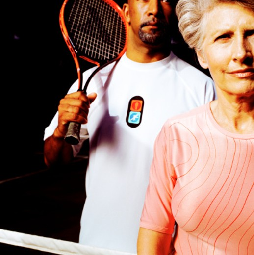 Stock Photo: 1491R-1128676 Close-up of an elderly woman and a man holding a tennis racket over his shoulder