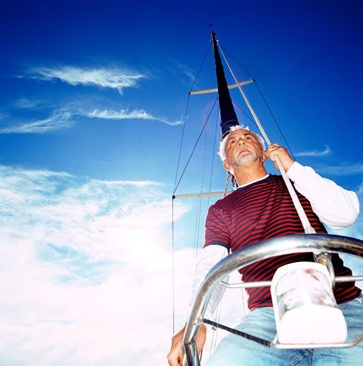 Low angle view of a man standing on a boat holding a mast line : Stock Photo