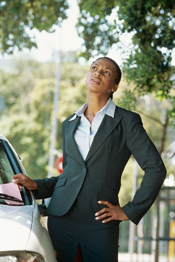 Stock Photo: 1491R-1129868 Young businesswoman taking a parking ticket from the windshield of her car