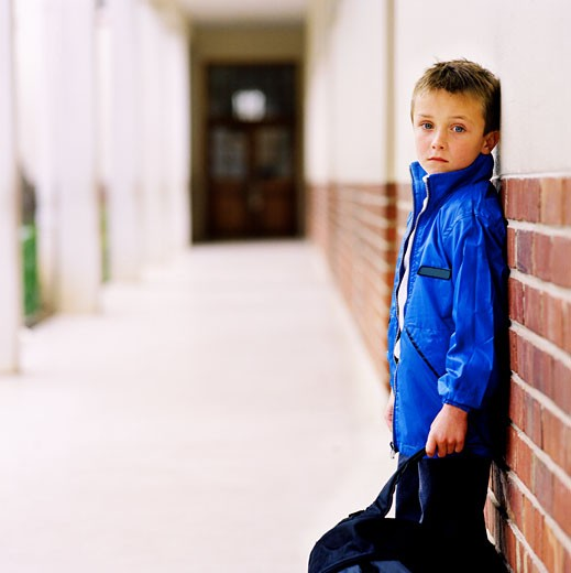 Stock Photo: 1491R-1130297 Side profile of a young boy (8-10) leaning against a wall in school