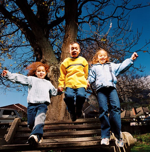 Low angle view of a group of children (6-10) jumping from a park bench : Stock Photo