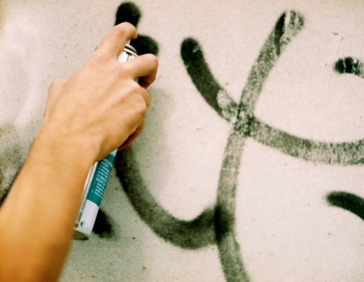 Close-up of a human hand spraying paint on a wall : Stock Photo