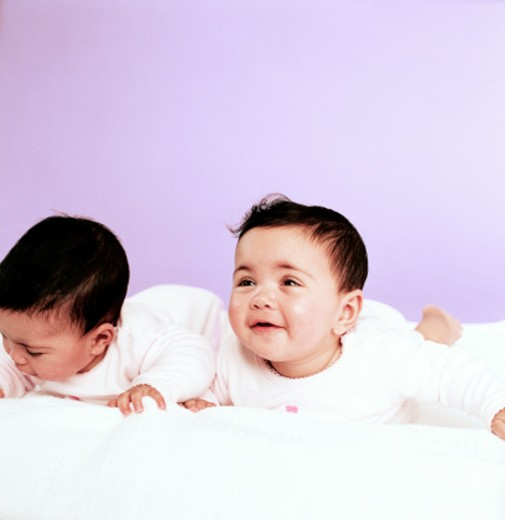 Close-up of two babies (6-12 months) lying on a bed on their stomachs : Stock Photo