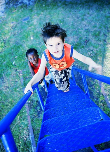Elevated view of a young boy (4-6) climbing the steps of a slide : Stock Photo