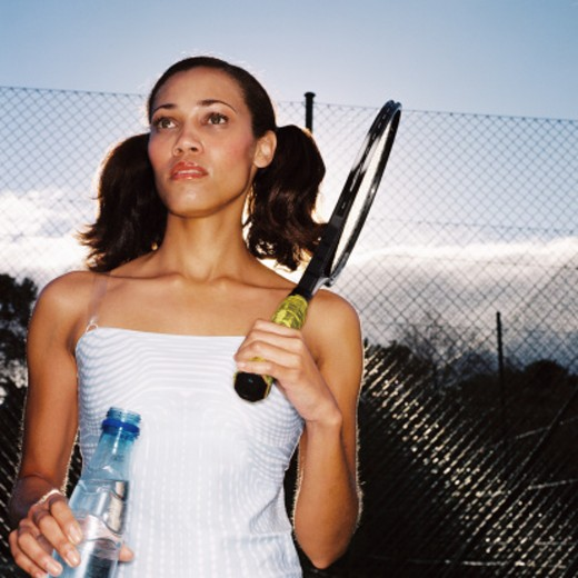 Stock Photo: 1491R-1131308 Low angle view of a young woman holding a tennis racket