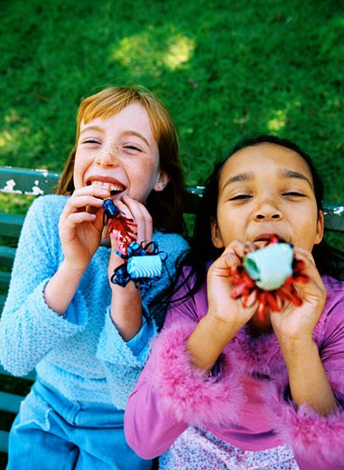 Stock Photo: 1491R-1131782 Two young girls (6-8) smiling blowing party whistles
