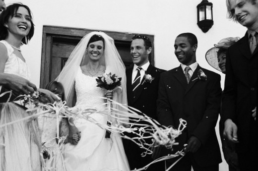 Stock Photo: 1491R-1132028 Low angle view of a bride and groom walking out of the church with people around them (black and white)