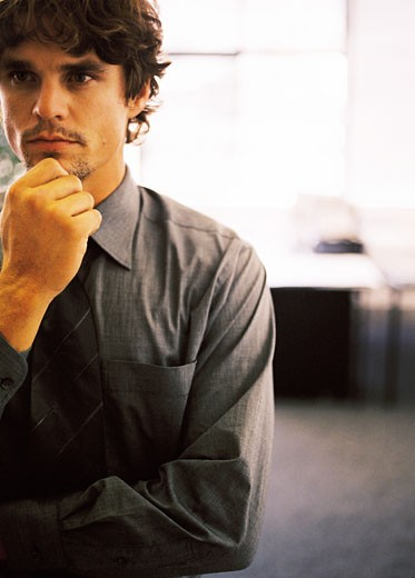 Close-up of a young man with his hand on his chin : Stock Photo