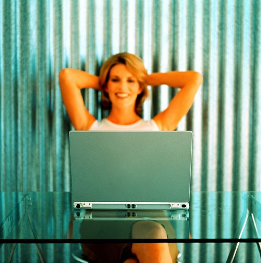 Close-up of a young woman sitting in front of a laptop : Stock Photo