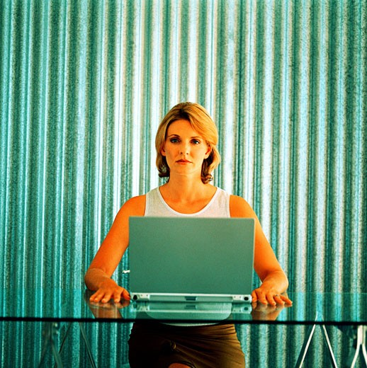 Portrait of a woman sitting in front of a laptop : Stock Photo