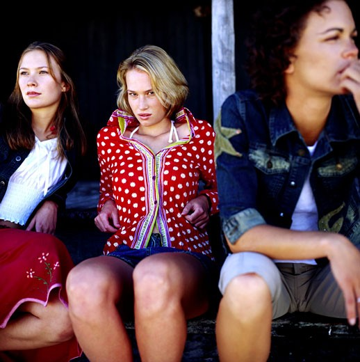Close-up of three young women sitting on steps : Stock Photo