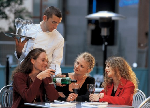 a male waiter serving a group of woman red wine : Stock Photo