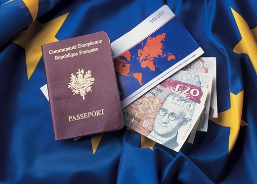Passport with a flight ticket and money on the flag of the European union : Stock Photo