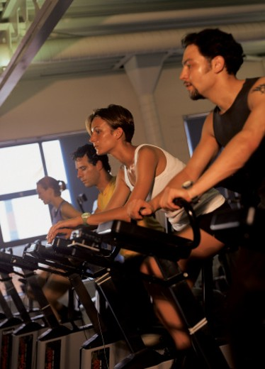 side profile of people working out on cycles in a gym : Stock Photo