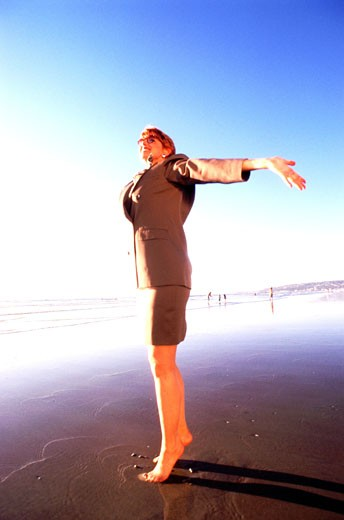 Businesswoman with arms outstretched on beach  : Stock Photo