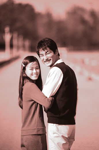 Stock Photo: 1491R-1137192 Young couple with arm in arm, smiling (Toned)