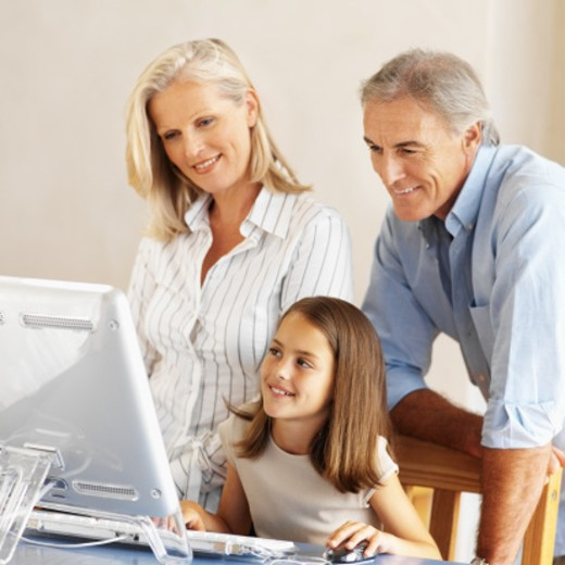 Young girl (12-13) working on a computer with her parents standing behind her : Stock Photo