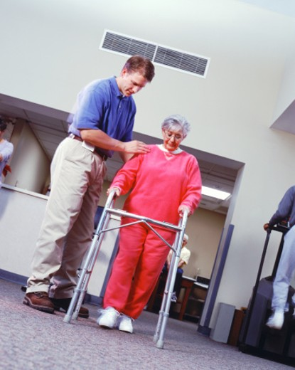 Stock Photo: 1491R-1146231 Physical therapist assisting senior woman with walking frame, low angle view