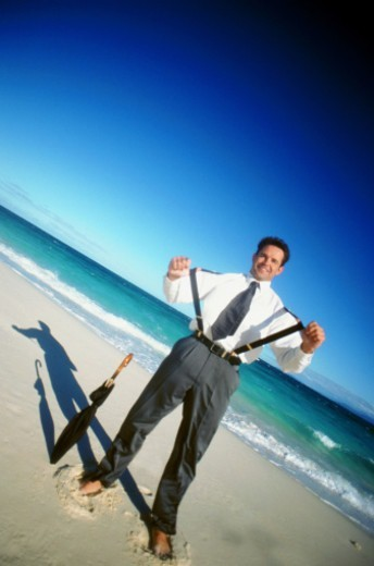Stock Photo: 1491R-1147558 Man standing on beach with umbrella, smiling