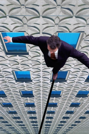 Businessman walking on tightrope, directly above : Stock Photo