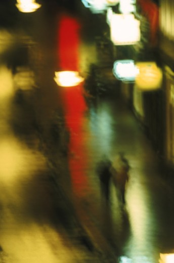 Two people on road at night (blurred motion) : Stock Photo