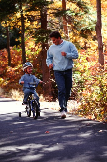 Stock Photo: 1491R-1150339 Father with son riding bicycle on road
