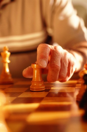 Stock Photo: 1491R-1150363 Woman playing chess, focus on hand