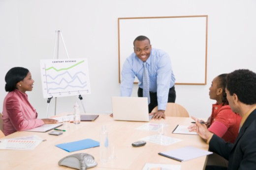Man giving presentation to colleagues in boardroom : Stock Photo