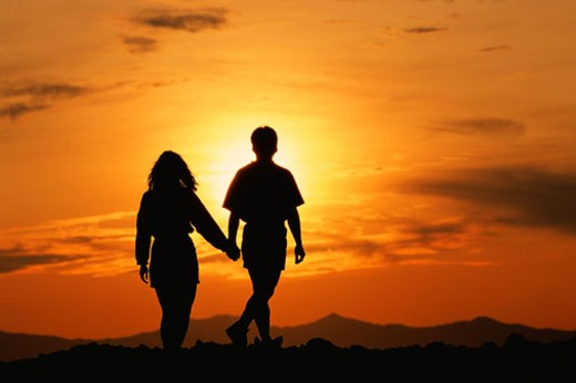 Silhouette of couple holding hands in front of mountain sunset : Stock Photo